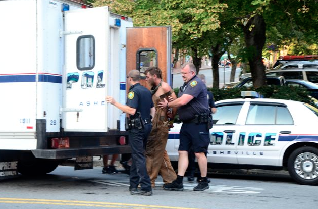 Asheville police arrest a man at the corner of North Lexington Avenue and Walnut Street in this September 2013 file photo/ Ashvegas/ Jason Sandford