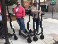 Passersby check out Bird electric scooters parked on the sidewalk along Biltmore Avenue on Oct. 25, the day the e-scooter company dropped about 200 of the scooters on Asheville city streets without first securing the proper city permissions. / photo by Jason Sandford