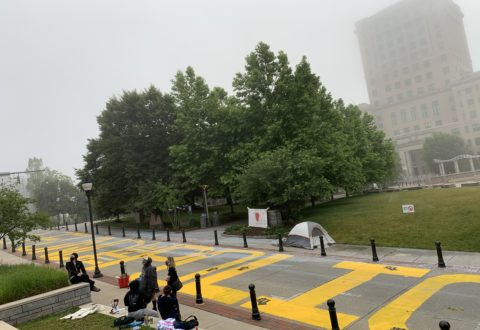 "A group of protesters stands by their ""Defund The Police"" mural on Spruce Street on Monday morning, June 22. The activists said that in the early morning hours, a group of armed counter-protesters showed up and tried to intimidate them and paint over their yellow-lettered message with blue paint. A city of Asheville crew arrived later Monday to wash away the mural./ photo by Jason Sandford"